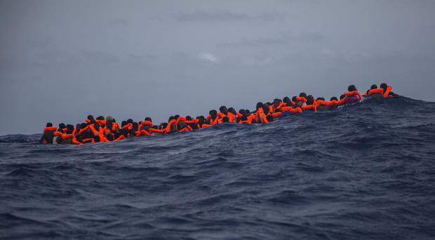 Migrants wait to be rescued by aid workers in the Mediterranean Sea (AP)