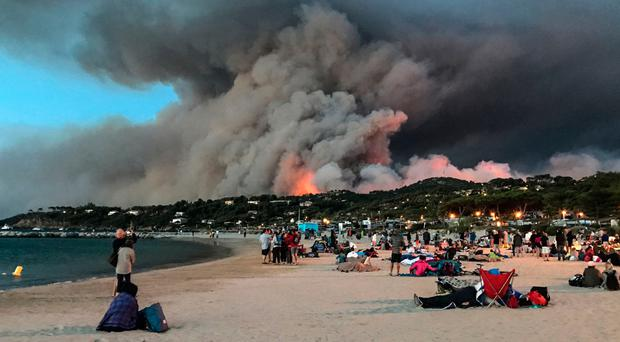 People take refuge on the beach as fire burns