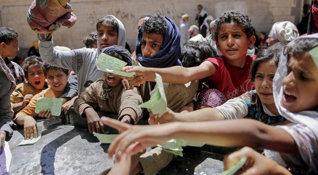 Yemenis present documents in order to receive food rations provided by a local charity in Sanaa (Hani Mohammed/AP)