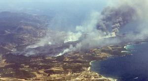 An aerial view shows plumes of smoke rising in the air from burning wildfires on the outskirts of Bormes-les-Mimosas, French Riviera (Nadine Achoui-Lesage/AP)