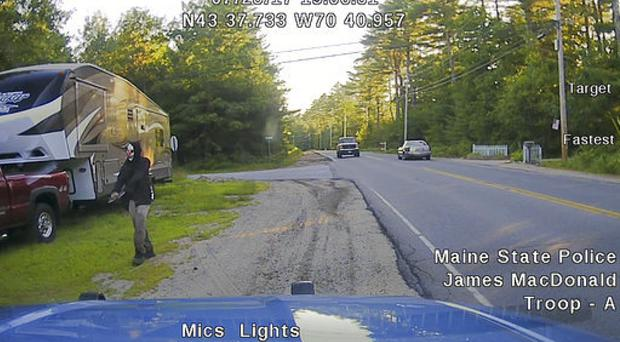 A police car dashboard camera image shows a man strolling down a street wearing a clown mask (Maine State Police via AP)