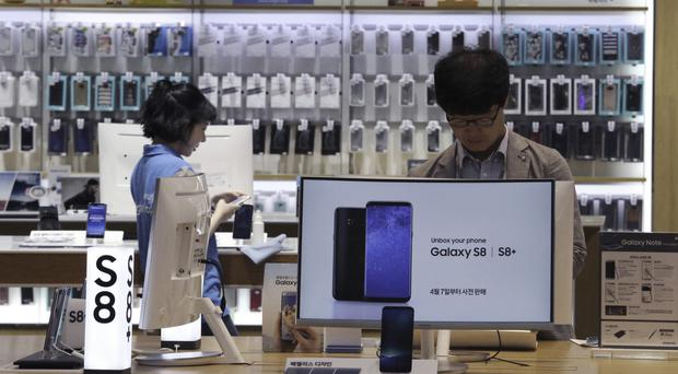 A visitor tries out Samsung Galaxy S8 smartphones at the electronics giant's shop in Seoul, South Korea (AP)