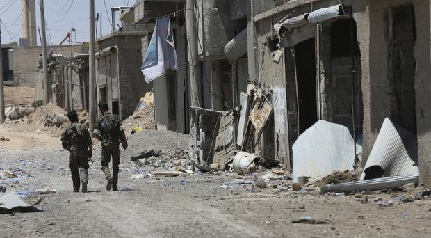 US-backed Syrian Democratic Forces fighters walk past destroyed shops in Raqqa