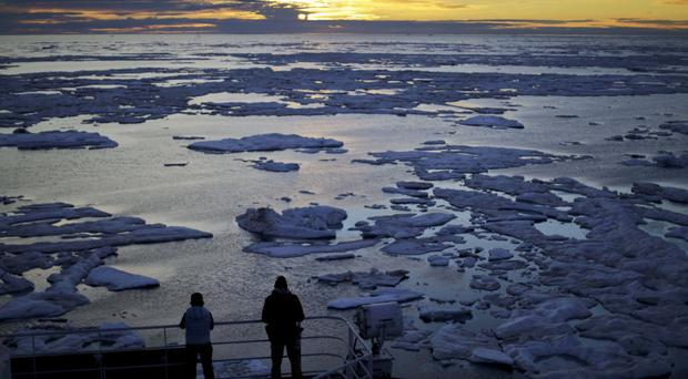 Researchers look out from the Finnish icebreaker MSV Nordica as the sun sets over sea ice floating on the Victoria Strait along the Northwest Passage (AP Photo/David Goldman)
