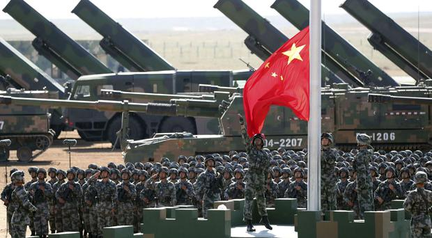 Chinese People's Liberation Army troops perform a flag-raising ceremony at a military parade to commemorate the 90th anniversary of the founding of the PLA (Pang Xinglei/Xinhua via AP)