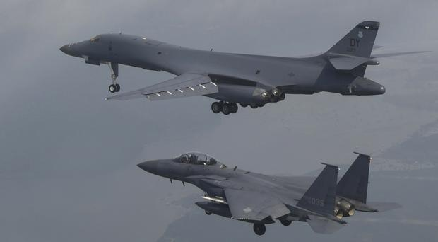 A US Air Force B-1 bomber top flies with South Korean fighter jets over South Korea