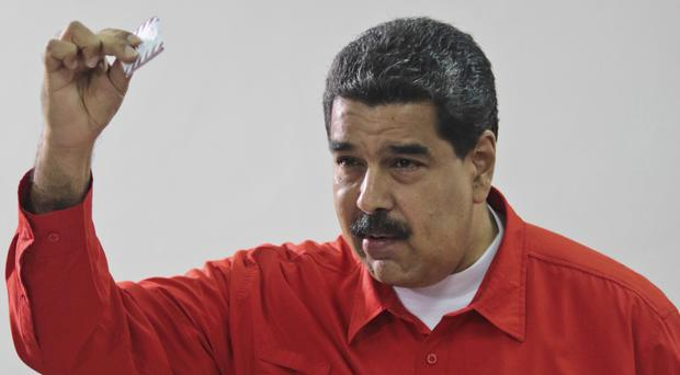 Nicolas Maduro shows his ballot after casting a vote for a constitutional assembly (Miraflores Press Office/AP)