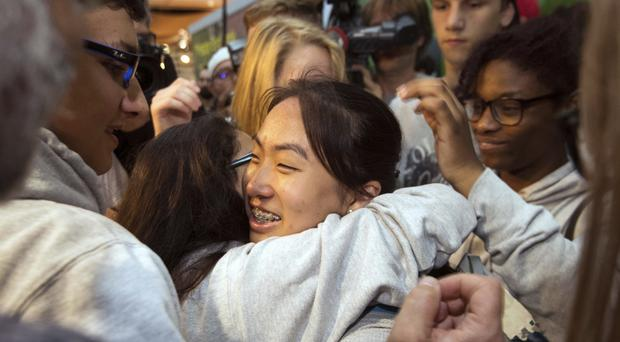 Schoolgirl Bivsi Rana is hugged by friends at Duesseldorf Airport (Marius Becker/dpa via AP)