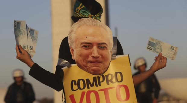 A woman holds fake Brazilian bank notes wearing a human billboard composed of an image of President Michel Temer during a protest in front of the National Congress in Brasilia (AP Photo/Eraldo Peres)