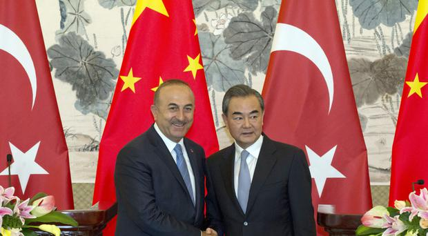 Turkish foreign minister Mevlut Cavusoglu meets his Chinese counterpart Wang Yat the Diaoyutai State Guesthouse in Beijing (AP)