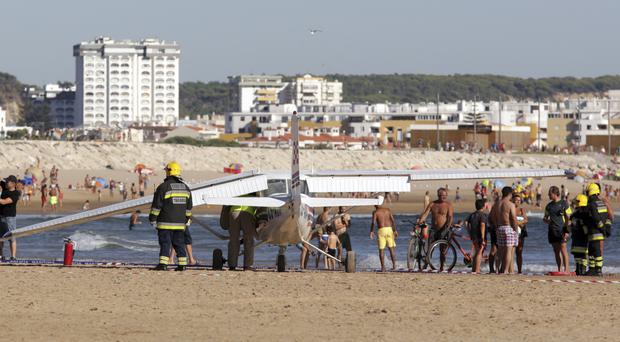 Firefighters stand next to a small plane which made an emergency landing on Sao Joao beach in Costa da Caparica (Armando Franca/AP)