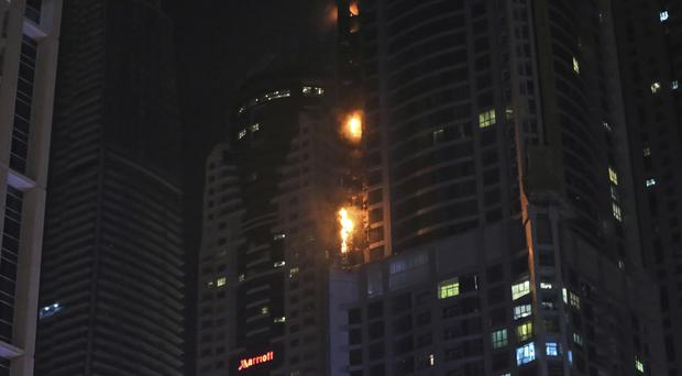 Smoke and fire rise from a high rise building in Marina district in Dubai (AP Photo/Kamran Jebreili)