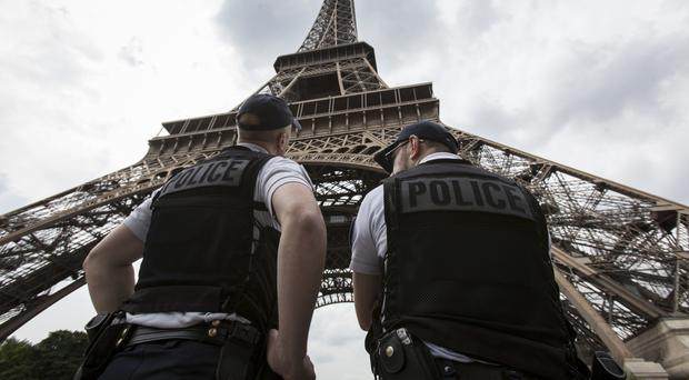 French riot police officers patrol under the Eiffel Tower in Paris. (AP)