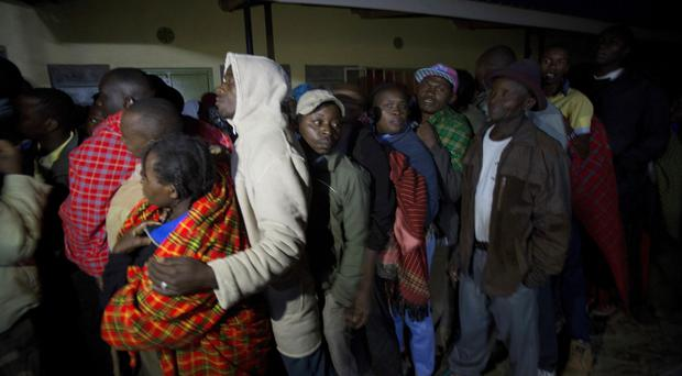 Early start: Maasai men line up before the opening of the polling stations in Bissil, south of Nairobi (AP)
