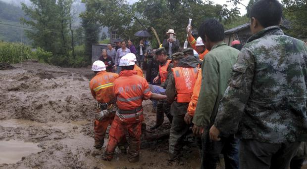 Rescuers carry a man injured in a landslide in Gengdi village in south-western China (Chinatopix/AP)
