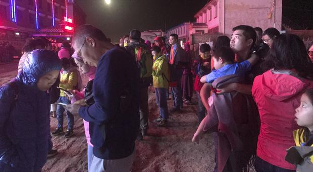 Evacuated tourists outside a hotel following the earthquake in Ruo'ergai in south-western China's Sichuan province (Chinatopix/AP)