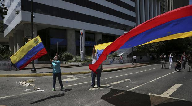 Anti-government demonstrators wave Venezuelan national flags during a protest against Nicolas Maduro in Caracas (AP)