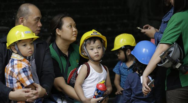 Children wear helmets as they evacuate a building after an earthquake was felt in the Philippines capital, Manila (AP Photo/Aaron Favila)