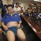 Democracy party member Howard Lam displays his wounds on his thighs. (AP)