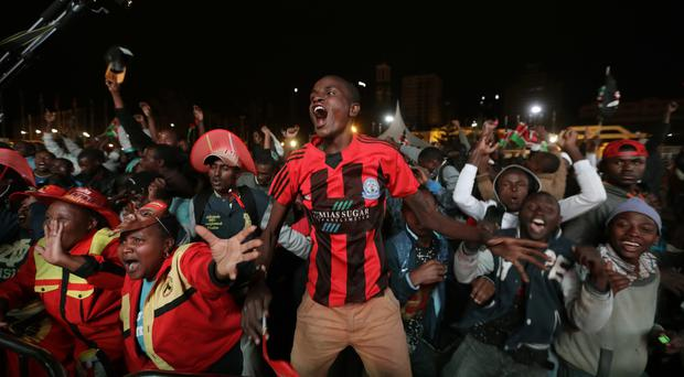 Supporters of Kenya's President Uhuru Kenyatta cheer the election results