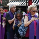 Mourners and clergy pray outside the memorial service for Heather Heyer (AP)