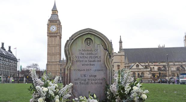 Amnesty International activists erect a six-feet-high gravestone in Parliament Square, London, in memory of thousands of Yemeni civilians killed by air strikes