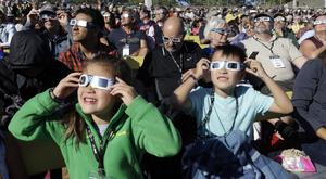 People wear protective glasses as they watch the beginning of the solar eclipse (AP/Don Ryan)