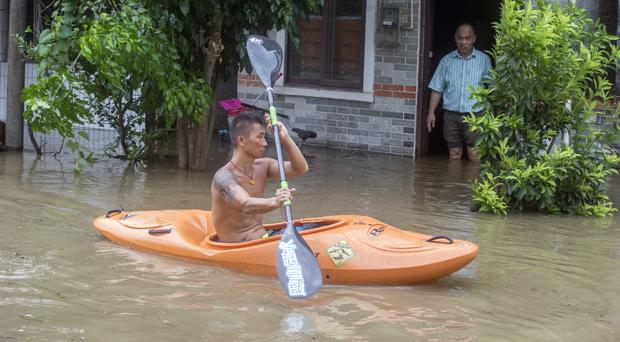 A man paddles a kayak along a flooded street in China caused by Typhoon Hato (Chinatopix Via AP)