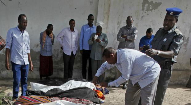 Somalis observe the bodies after they were taken to and displayed in the capital Mogadishu (AP)
