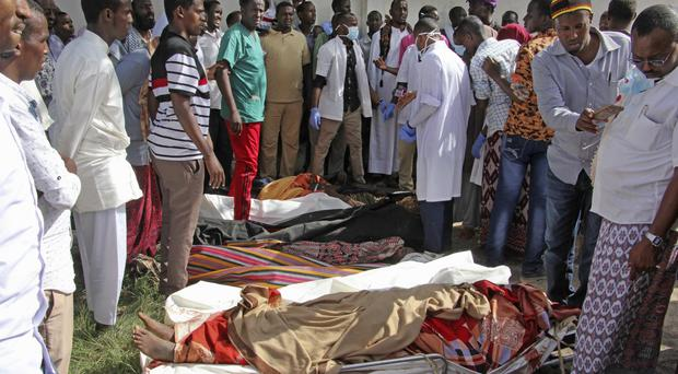 Somalis observe bodies which were brought to and displayed in the capital Mogadishu, Somalia (AP)