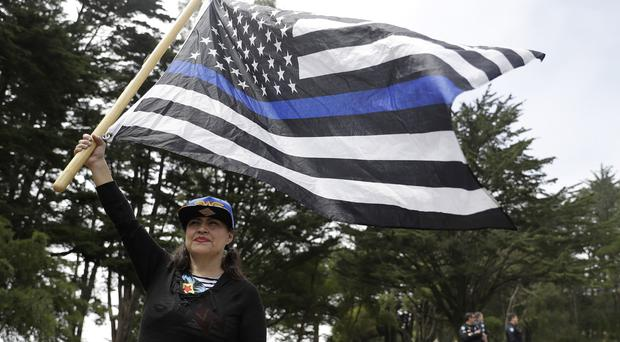 Laura Zulema waves a flag in support of the group Patriot Prayer during the news conference in Pacifica (AP)