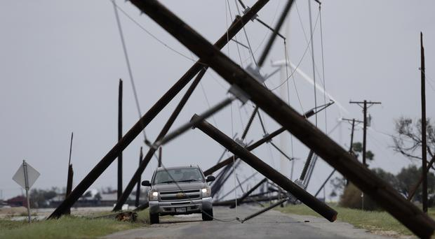 A driver tries to negotiate a maze of downed power lines in Taft, Texas (AP)