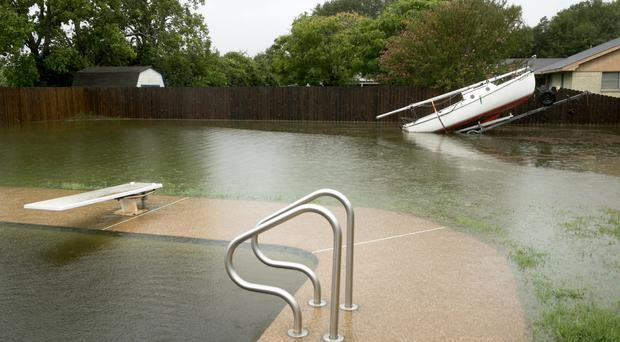 Swim for it: A flooded back garden in Smithville, Texas (Austin American-Statesman/AP)