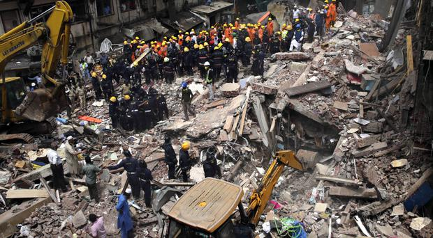 Rescuers work at the site of a building that collapsed in Mumbai after torrential rains lashed western India (AP Photo/Rafiq Maqbool)