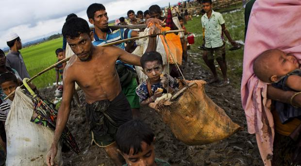 A Rohingya refugee carries a child in a sack after crossing over to the Bangladesh side of the border (AP/Bernat Armangue)