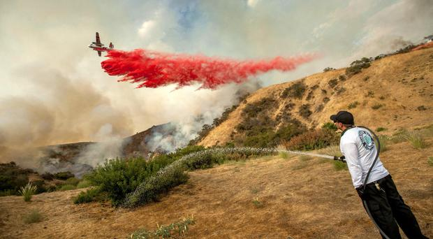A man waters down a hillside as a plane makes a drop in Sun Valley, north of Los Angeles (Paul Rodriguez/The Orange County Register via AP)