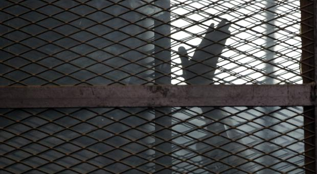 A Muslim Brotherhood member gestures from a cage in a courtroom in Torah prison, southern Cairo, Egypt (AP)