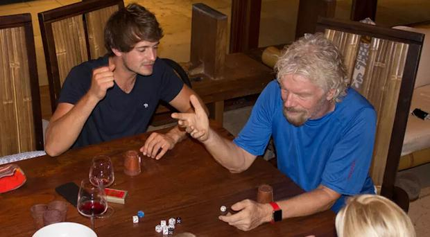 Sir Richard Branson, right, plays a game of Perudo as he camps out on his private island of Necker as Hurricane Irma nears (Virgin.com/PA)