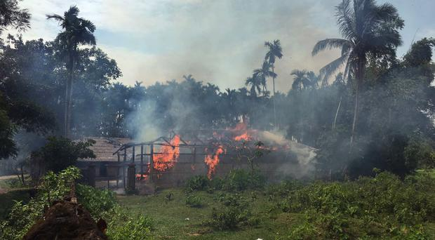 Fire engulfs homes in Gawdu Zara village after it was abandoned by Rohingya Muslims (AP)
