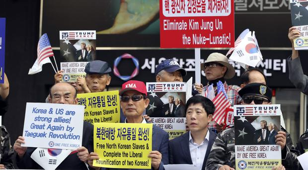 South Korean activists and North Korean defectors hold signs during a rally against Pyongyang (AP)
