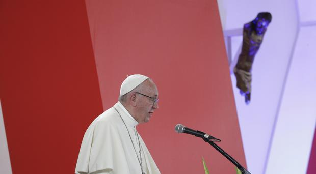 Pope Francis speaks below a mutilated statue of Christ from a church destroyed in a rebel mortar attack 15 years ago (AP)