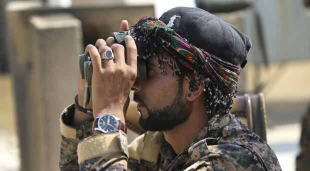 An Arab fighter with the US-backed Syrian Democratic Forces looks through his binoculars to an air strike that hit an IS militant group position, in Raqqa, Syria (AP)