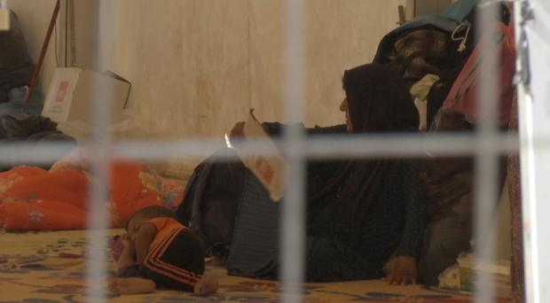 A woman and a small child lie on the floor of a tent in a camp for displaced people (AP/Balint Szlanko)