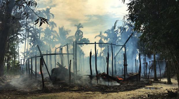 Smoke rises from a burned house in Gawdu Zara village, northern Rakhine state, Burma (AP)