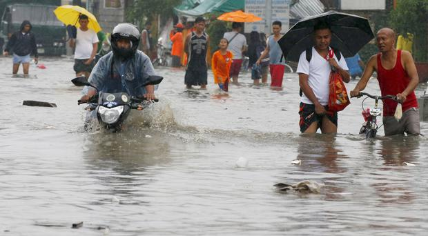 Residents wade through a flooded road in Cavite province, south of Manila (AP)
