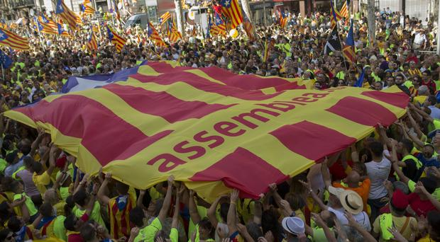 People holds up a giant estelada or independence flag during the Catalan National Day in Barcelona, Spain, on Monday (AP)