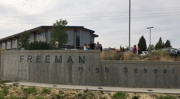 People gather outside Freeman High School after reports of a shooting (KHQ via AP)
