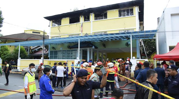 Police and rescue personnel work at school cordoned off after the fire on the outskirts of Kuala Lumpur (AP)