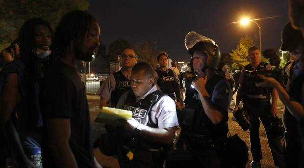 Police talk to protesters following demonstration over acquittal of a former St Louis police officer charged with murdering a black man (AP)