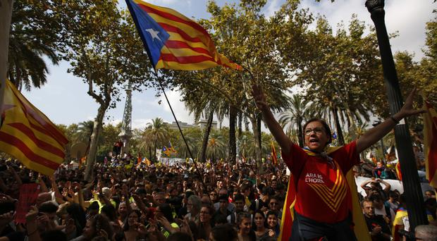 A woman gestures as others wave the ''estelada'' or Catalonia independence flags during a protest in Barcelona, Spain (AP)